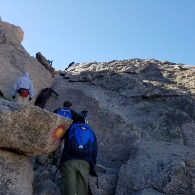 Climbers getting by the choke stone at the top of the Trough