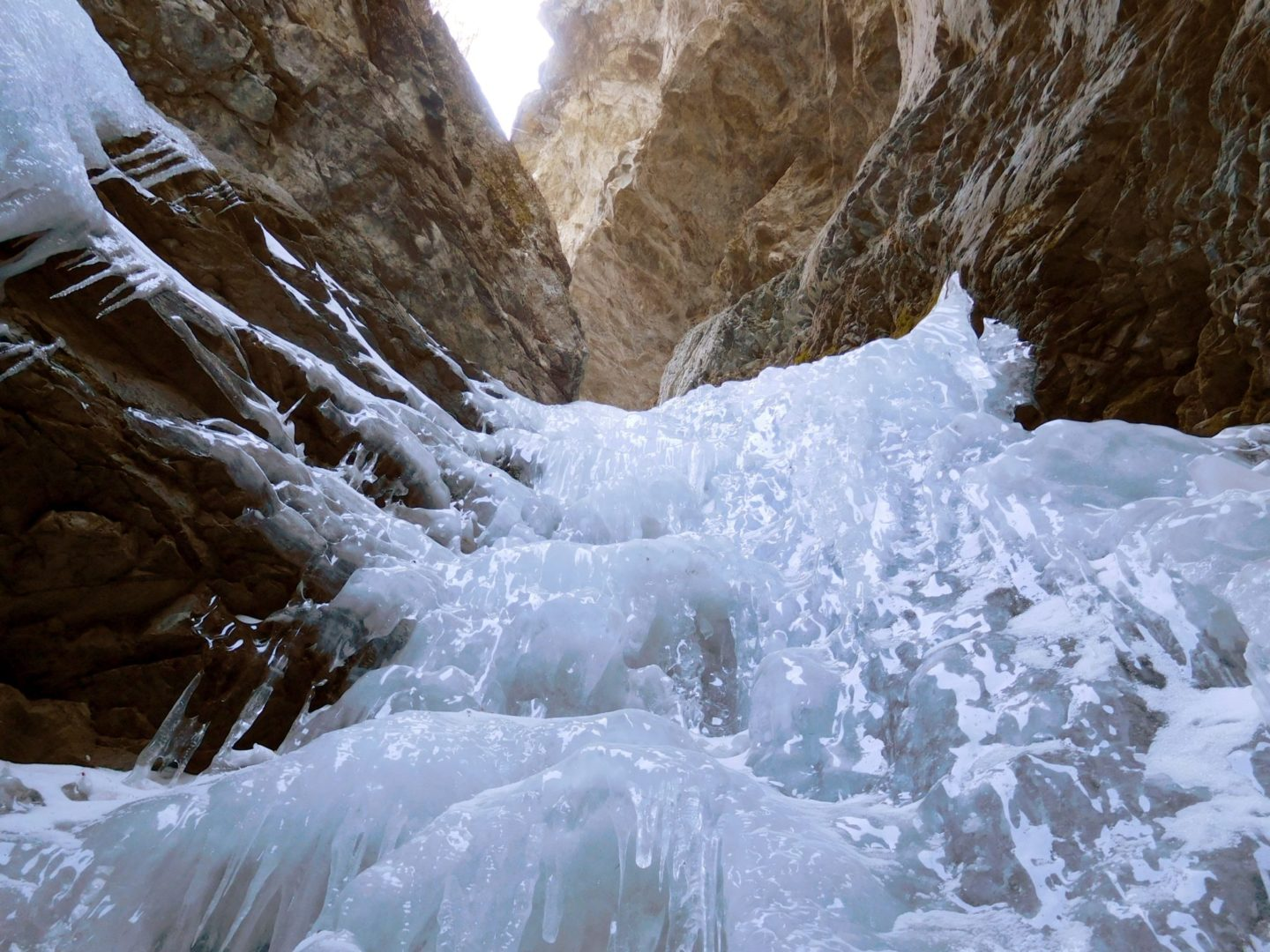 Looking up the frozen falls you can hear water still running underneath